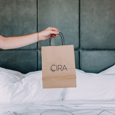 Someone holds up a takeout bag from Cira above a bed in the hotel