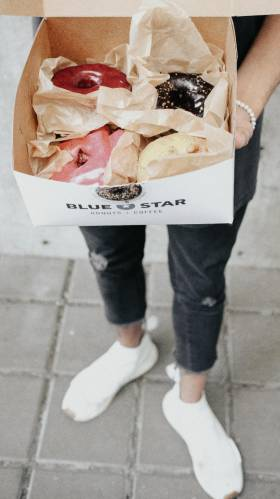 Someone wearing ripped jeans and white sneakers holds out a box of donuts of varying colours