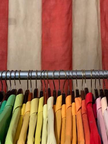 A rack of very brightly coloured shirts, from green through yellow, orange, red and pink