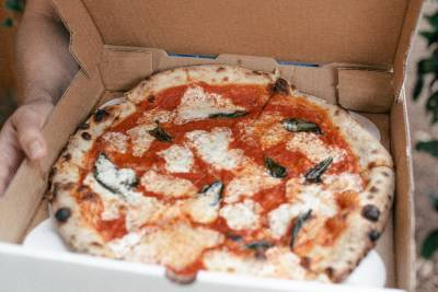 An open takeout box with pizza inside of it, with mozzarella and basil toppings