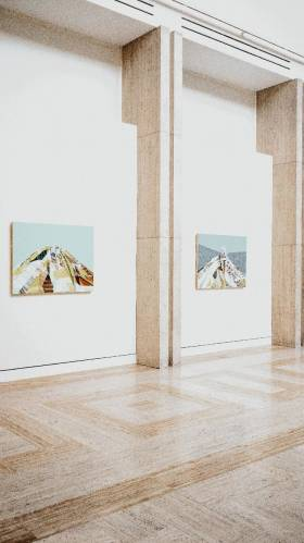 Two pieces of artwork depicting mountains on a wall in the Portland Art Museum