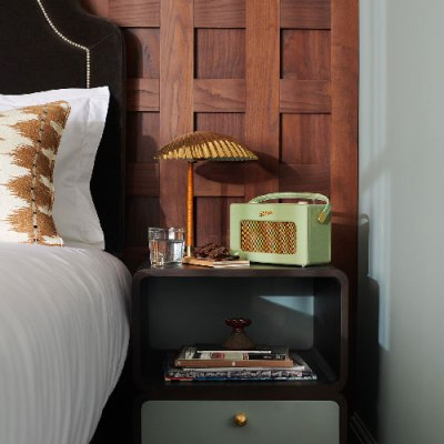 Green Roberts radio and lamp sit on bedside table in a hotel room