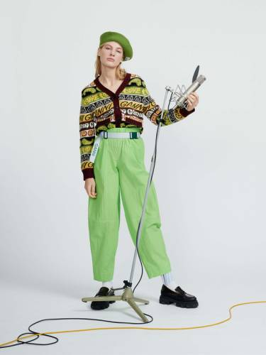 Woman in bright green trousers and a patterned cardigan holding a microphone
