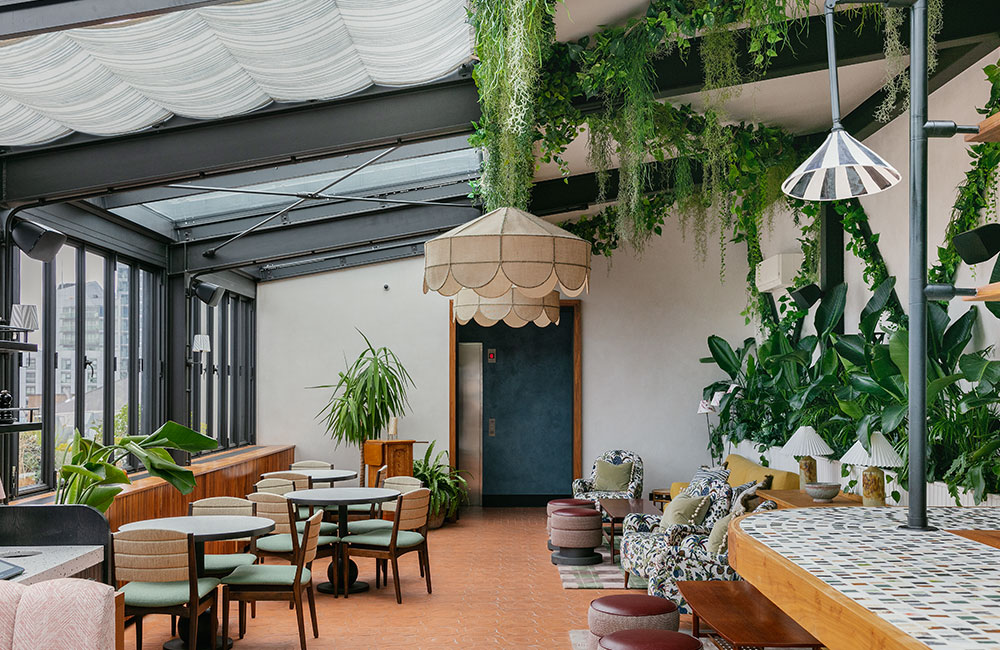 The restaurant has a lot of plants and a glass roof