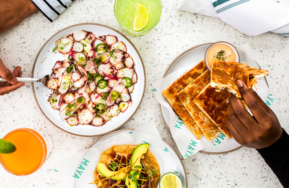 Octopus ceviche and tostadas served alongside cocktails on a table